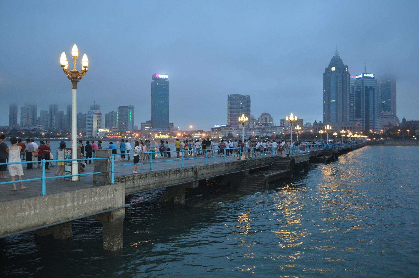 """位于市委,市政府大楼南,香港中路与东海西路之间,是城市东部新的休闲旅游中心。广场以东海路为界分为南北两部分,中轴线上市政府办公大楼、隐式喷泉、点阵喷泉、""""五月的风""""雕塑及海上百米喷泉,富于节奏地展现出庄重、坚实、蓬勃向上的壮丽景象,在大面积草坪和风景林衬托下,更加生机勃勃,充满现代气息。主体雕塑""""五月的风""""以螺旋上升的风的造型和火红的色彩,充分体现了""""五四运动""""反帝反封建的爱国主义基调和张扬腾升的民族力量。作品与周围海天自然环境以及园"""